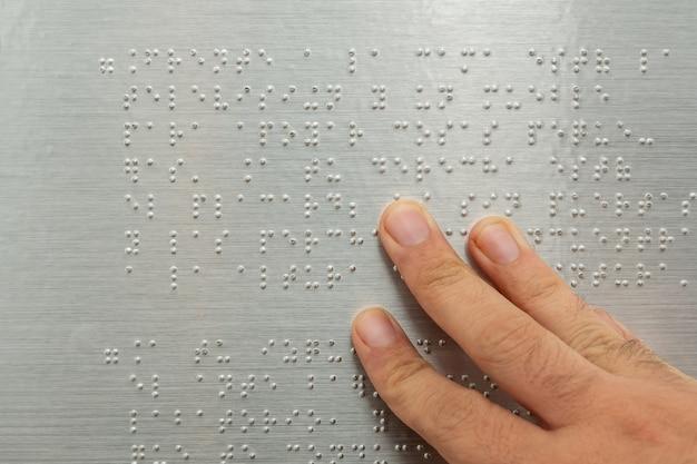 Zbliżenie męskiej ręki czytanie tekstu w alfabecie braille'a