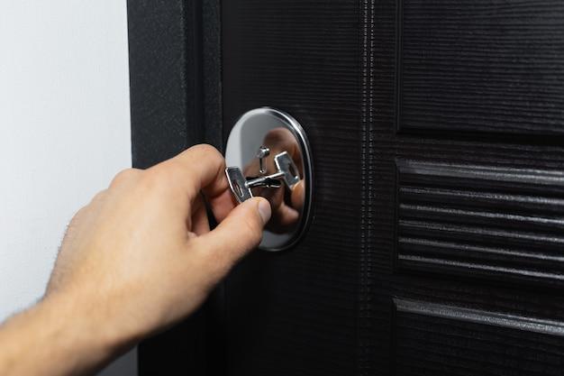 Zbliżenie męskiej ręki odblokowującej lub blokującej zamek nowoczesnych drzwi domu z kluczem.