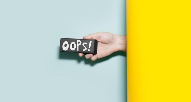 Zbliżenie męskiej ręki trzymającej małą czarną tablicę z tekstem ups