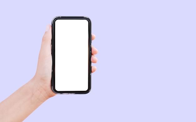 Zbliżenie: męskiej ręki trzymającej smartfon z białą makietą na białym tle na pastelowy fiolet z miejsca na kopię.