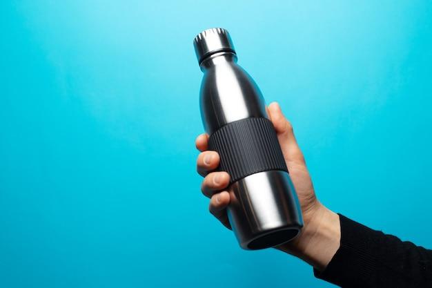 Zbliżenie: męskiej ręki trzymającej stalową butelkę termiczną wielokrotnego użytku