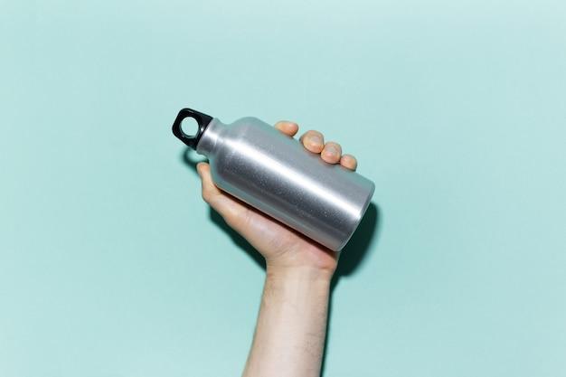 Zbliżenie: męskiej ręki trzymającej wielokrotnego użytku, aluminiowa butelka termiczna do wody, na tle studio koloru cyjan, aqua menthe. zero marnowania. nie zawiera plastiku.