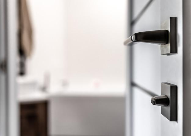 Zbliżenie: metalowa klamka na niewyraźne tło wnętrza domu.