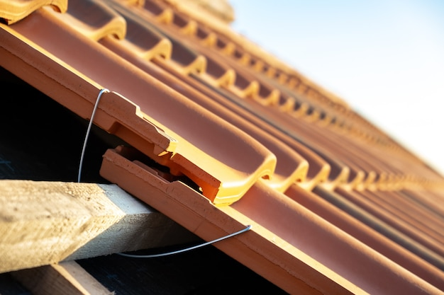 Zbliżenie metalowej kotwy montażowej do montażu żółtych dachówek ceramicznych montowanych na deskach pokrywających dach budynku mieszkalnego w trakcie budowy.