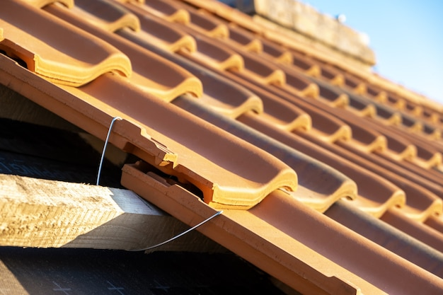 Zbliżenie metalowej kotwy montażowej do montażu żółtych dachówek ceramicznych zamontowanych na drewnianych deskach pokrywających dach budynku mieszkalnego w budowie.