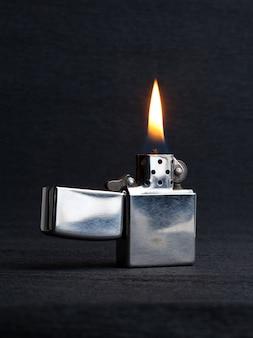 Zbliżenie metalowej zapalniczki gazowej z płonącym ogniem na szarym tle z miejscem na kopię
