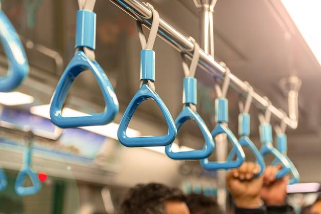 Zbliżenie metra lub poręczy metra, ręka trzyma niebieską poręcz