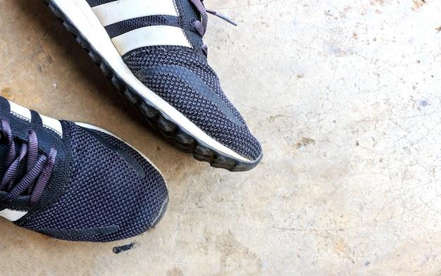 Zbliżenie mężczyzna buty na cementowej podłoga, odgórnym widoku i nadmiernym świetle ,.