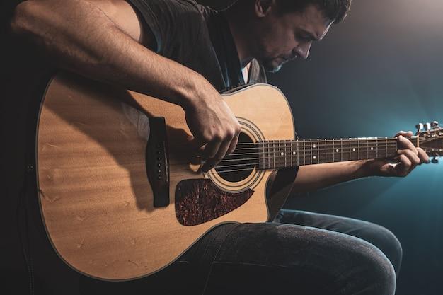 Zbliżenie: mężczyzna grający na gitarze akustycznej w ciemności z oświetleniem scenicznym.