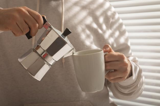 Zbliżenie mężczyzna leje kawę w biurze w letni dzień