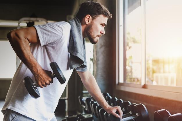 Zbliżenie mężczyzna mienia dumbbell zdrowego treningu i budynku ciało przy gym sprawnością fizyczną