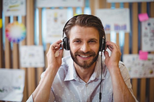 Zbliżenie: mężczyzna projektant graficzny słuchanie muzyki na słuchawkach
