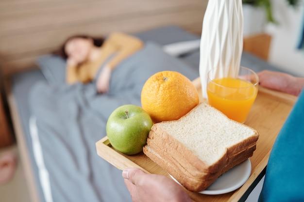 Zbliżenie: mężczyzna przynoszący tacę z kanapką, sokiem pomarańczowym i owocami w łóżku, w którym śpi jego żona w walentynkowy poranek