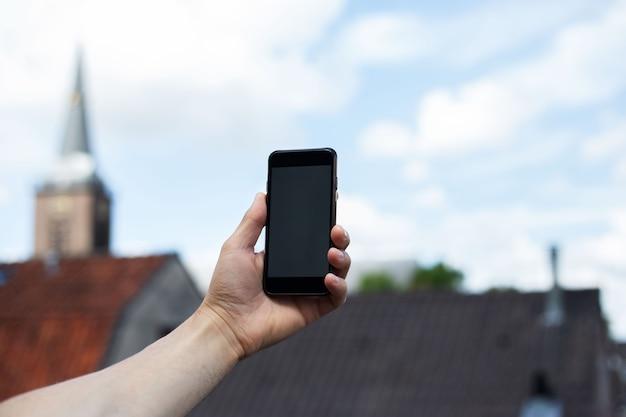 Zbliżenie: mężczyzna ręka trzymać smartfona na powierzchni starego miasta.