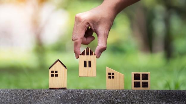 Zbliżenie mężczyzna ręka wybierając model domu na tle przyrody i planuje kupić nieruchomość