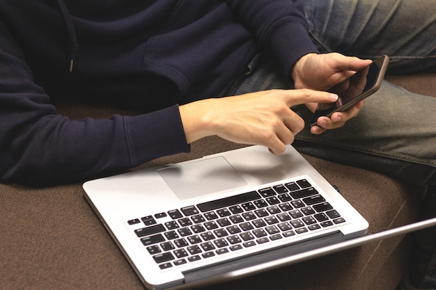 Zbliżenie mężczyzna relaksuje używać smartphone i laptopu obsiadanie na kanapie.