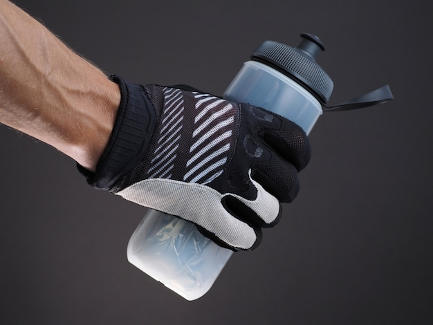 Zbliżenie: mężczyzna rowerzysta ręki trzymającej plastikową butelkę wody termo na ciemno