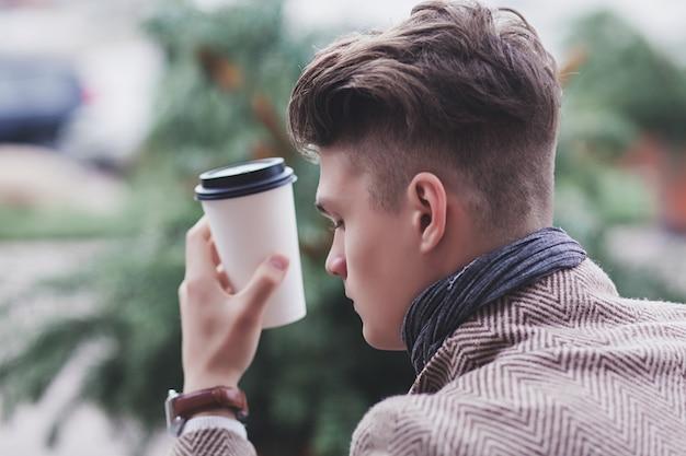 Zbliżenie: mężczyzna trzyma kawę na wynos w mieście