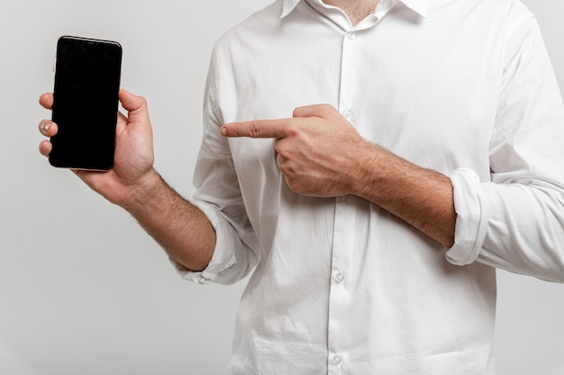 Zbliżenie mężczyzna trzyma pusty ekran smartfona i wskazuje na na białym tle na białej makiecie
