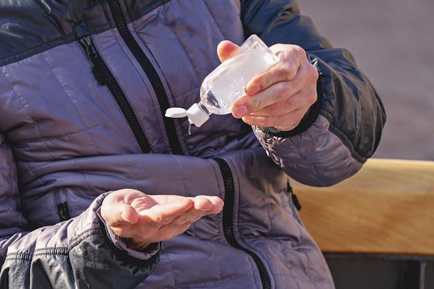 Zbliżenie mężczyzna używa żel dezynfekujący na rękach