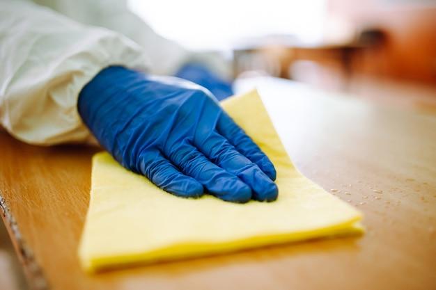 Zbliżenie: mężczyzna z grupy dezynfekcji czyści żółtą szmatką biurko w szkole. profesjonalny pracownik sterylizuje klasę, aby zapobiec rozprzestrzenianiu się covid-19. opieka zdrowotna uczniów i studentów.