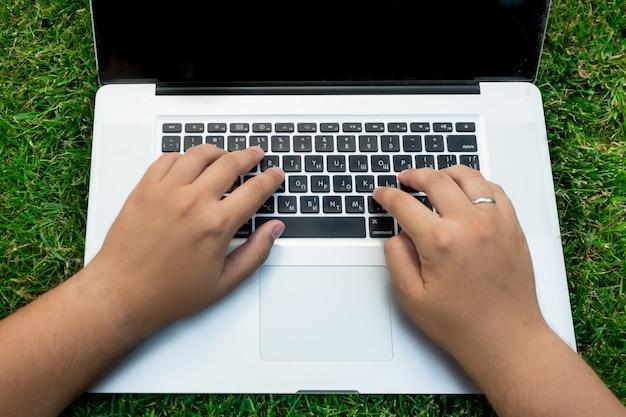 Zbliżenie mężczyzna za pomocą laptopa na zielonej trawie
