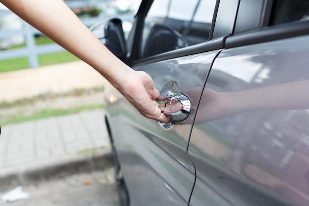 Zbliżenie mężczyzny otwiera drzwi samochodu.