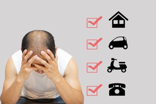 Zbliżenie mężczyzny siedzącego z rękami w głowie na stresujące warunki zadłużenia