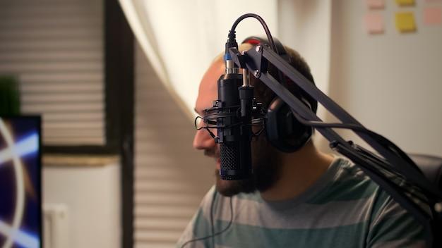 Zbliżenie mężczyzny streamera rozmawiającego do mikrofonu z innymi graczami podczas turnieju kosmicznej strzelanki