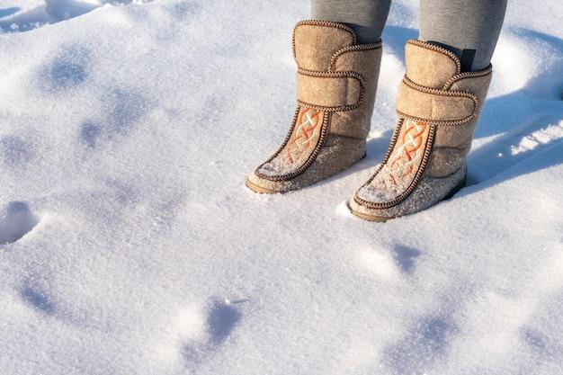 Zbliżenie mężczyzny w filcowych butach stojącego na śniegu.