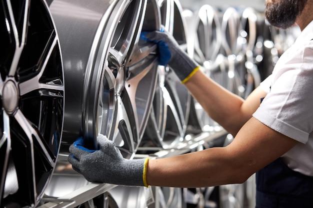 Zbliżenie mężczyzny w rękawiczkach zdejmujących felgi samochodowe z regału, przycięty mechanik samochodowy w mundurze w pracy