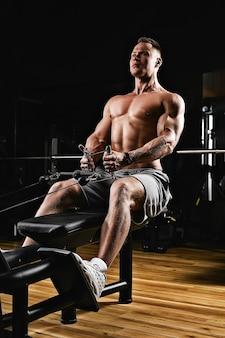 Zbliżenie mężczyzny z nagim tułowiem wykonującego ćwiczenia mięśni pleców na symulatorze w hali sportowej
