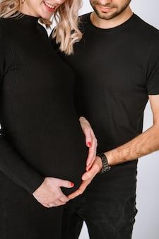 Zbliżenie mężczyzny z rękami na brzuchu kobiety w ciąży