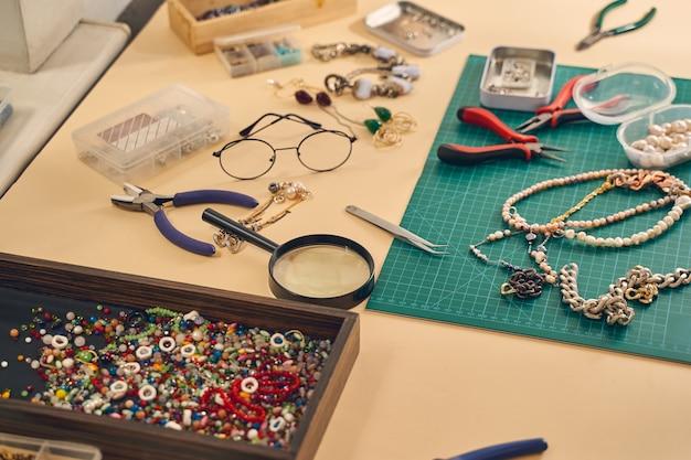 Zbliżenie miejsca pracy przy robieniu biżuterii poprzez nawlekanie koralików na drut za pomocą szczypiec jubilerskich