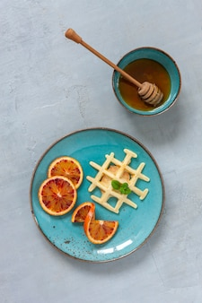 Zbliżenie: miękkie wiedeńskie gofry na talerzu z jagodami, truskawkami i honney