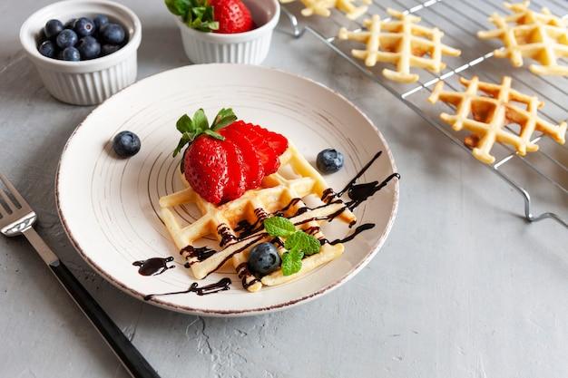 Zbliżenie: miękkie wiedeńskie gofry na talerzu z jagodami, truskawkami i sosem czekoladowym