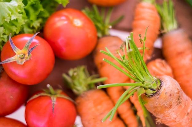 Zbliżenie mieszanych kolorowych warzyw, takich jak marchewki i pomidory oraz sałatki w wielu kolorach i zdrowej koncepcji stylu życia dla diety i dobrego samopoczucia