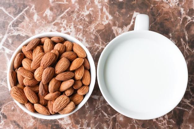 Zbliżenie migdałów i mleko migdałowe w białym kubku, alternatywa dla produktu wegetariańskiego