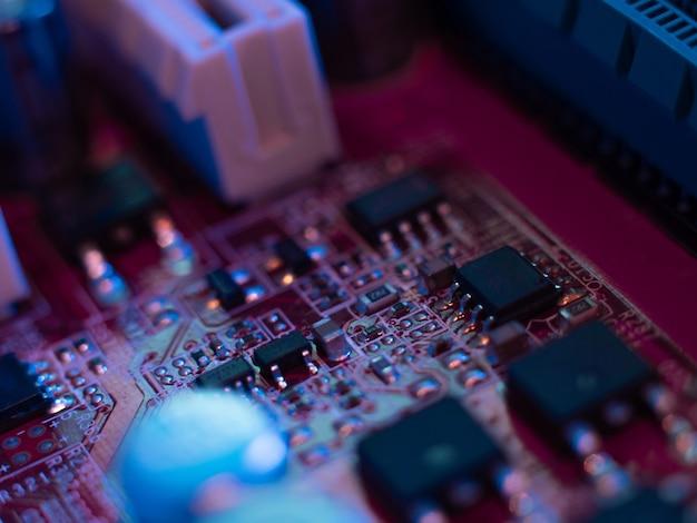 Zbliżenie mikroukładów płyty głównej komputera w kolorowym oświetleniu
