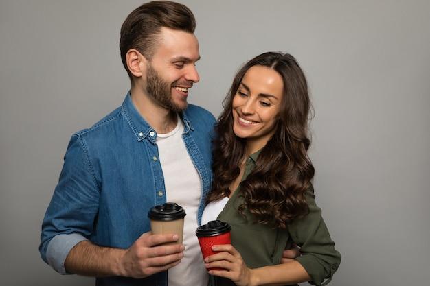 Zbliżenie: miła dziewczyna z długimi kasztanowymi włosami, przystojny mężczyzna z brodą, przytulający się, trzymający dwie filiżanki kawy i patrzący na siebie życzliwie.