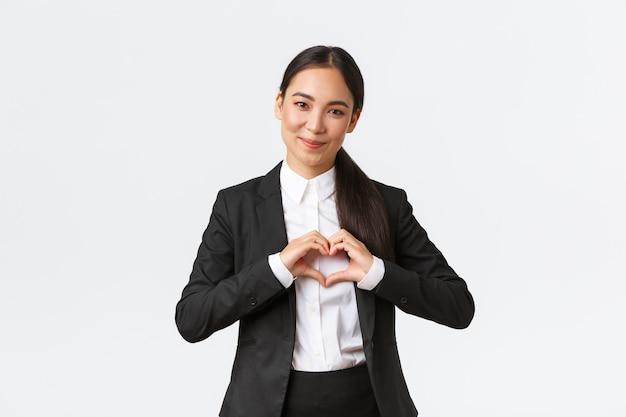 Zbliżenie miłej azjatyckiej sprzedawczyni bizneswoman w czarnym garniturze, która dba o swoich klientów pokazując serce ...