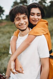 Zbliżenie miłości para zabawy podczas randek na świeżym powietrzu. piękna młoda para, podczas gdy mężczyzna jest na baranie jej dziewczyną.