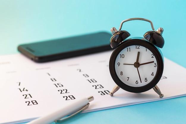 Zbliżenie mini budzik, kalendarz i białe pióro