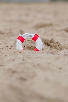 Zbliżenie Miniaturowe Koło Ratunkowe Kopać W Piasku Na Plaży. Premium Zdjęcia