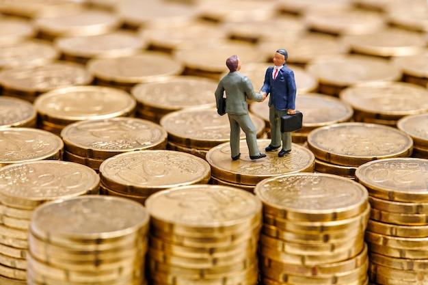 Zbliżenie miniaturowych męskich przedsiębiorców stojących na stosie centów euro i ściskając ręce podczas osiągania porozumienia w sprawie transakcji