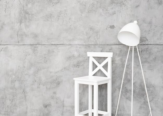 Zbliżenie minimalistycznej białej lampy podłogowej i taboretu z betonowymi panelami