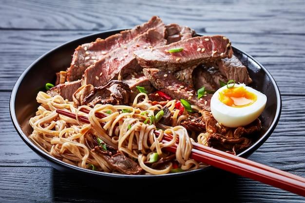 Zbliżenie miski makaronu soba z krojonym stekiem z rostbefu, grzybami shiitake, połową jajka na twardo i smażonymi warzywami z pałeczkami, kuchnia azjatycka, widok poziomy z góry