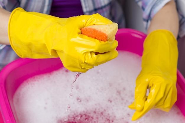 Zbliżenie miski z wodą z mydłem, ręce w gumowych rękawicach ochronnych z gąbką.