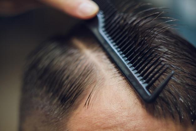Zbliżenie, mistrz fryzjer robi fryzurę i styl za pomocą nożyczek i grzebienia. concept barbershop.