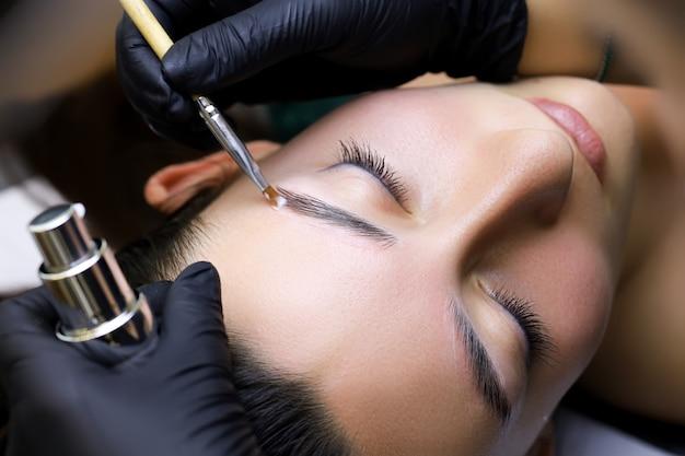 Zbliżenie mistrza grzebie szczoteczką brwi modelki po zabiegu długotrwałej stylizacji brwi